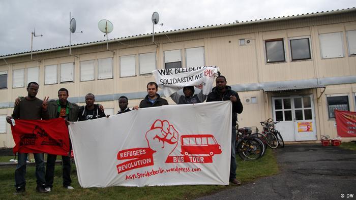 Flüchtlinge mit Transparenten vor einer Flüchtlingsunterkunft (Foto: DW/Stephanie Höppner)