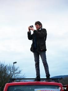 Ein Aktivist steht auf einem Kleinbus und macht Fotos (Foto: DW/Stephanie Höppner)