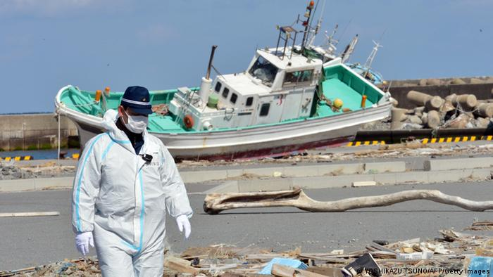 A police officer walks on a pier to search for missing people as a wrecked ship (back) still rests grounded in Namie, near the striken TEPCO's Fukushima Dai-ichi nuclear plant in Fukushima prefecture on March 11, 2013. March 11, 2013 marks the second anniversary of the 9.0 magnitude earthquake that sent a huge wall of water into the coast of the Tohoku region, splintering whole communities, ruining swathes of prime farmland and killing nearly 19,000 people. AFP PHOTO / YOSHIKAZU TSUNO (Photo credit should read YOSHIKAZU TSUNO/AFP/Getty Images)