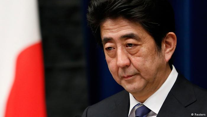Japan's Prime Minister Shinzo Abe attends a news conference next to the national flag, which is hung with a black ribbon as a symbol of mourning for victims of the March 11, 2011 earthquake and tsunami, at his official residence in Tokyo March 11, 2013. Japan honoured the victims of its worst disaster since World War Two on Monday: the March 11, 2011 earthquake, tsunami and nuclear crisis that killed almost 19,000 people and stranded 315,000 evacuees, including refugees who fled radiation from the devastated Fukushima atomic plant. REUTERS/Yuya Shino (JAPAN - Tags: POLITICS DISASTER ANNIVERSARY)