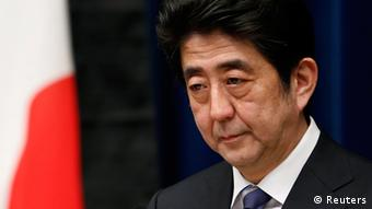 Japan's Prime Minister Shinzo Abe attends a news conference next to the national flag, which is hung with a black ribbon as a symbol of mourning for victims of the March 11, 2011 earthquake and tsunami, at his official residence in Tokyo March 11, 2013 (Photo: REUTERS/Yuya Shino)