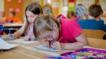 Девочка с синдромом Дауна на уроке в классе