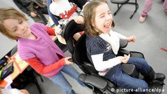 Одна ученица катит другую ученицу в инвалидном кресле