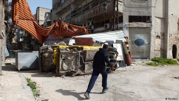 A man runs to take cover, past damaged cars and a curtain to be used as cover from snipers loyal to Syria's President Bashar al-Assad, in the besieged area of Homs March 9, 2013. Picture taken March 9, 2013. REUTERS/Yazan Homsy (SYRIA - Tags: POLITICS CIVIL UNREST)