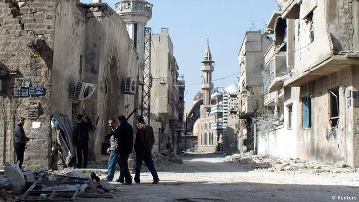 Free Syrian Army fighters inspect damages at the besieged area of Homs March 9, 2013.
