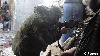 A Free Syrian Army fighter points his weapon as others take position in the Al-Khalidiya neighbourhood of Homs Photo: REUTERS/Muhammad Ibrahim/Shaam News Network/Handout