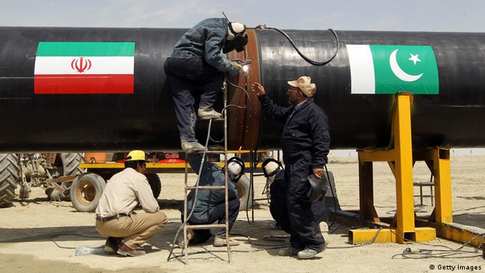 Iranians work on a section of a pipeline (on with are sticked Iranian and Pakistanese national flags) after the project was launched during a ceremony with presidents of Iran and Pakistan on March 11, 2013 in the Iranian border city of Chah Bahar.