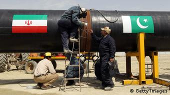 Iranians work on a section of a pipeline (on with are sticked Iranian and Pakistanese national flags) after the project was launched during a ceremony with presidents of Iran and Pakistan on March 11, 2013 in the Iranian border city of Chah Bahar (Photo: ATTA KENARE/AFP/Getty Images)