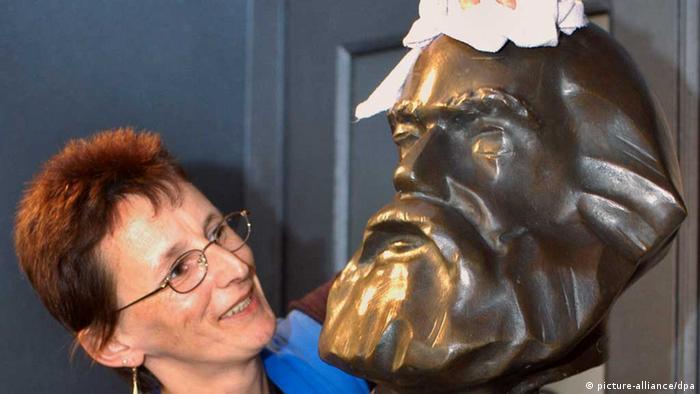 Уборщица вытирает пыль с бюста Карла Маркса