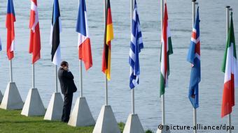 Berlusconi stands alone alongside various nations' flags (c) Ronald Wittek/dpa