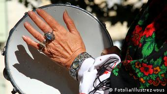 A hand bedecked with rings claps a drum