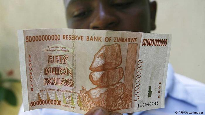 A Zimbabwean looks at a new 50 billion dollar bank note issued by Zimbabwe's central bank