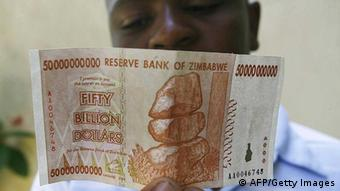 A Zimbabwean looks at a new 50 billion dollar bank note issued by Zimbabwe's central bank on January 13, 2009. The bank has been introducing new banknotes every month sometimes more than once a month as the country battles to catch up with runaway inflation fast eroding the value of the local currency. AFP PHOTO/Desmond Kwande (Photo credit should read DESMOND KWANDE/AFP/Getty Images)