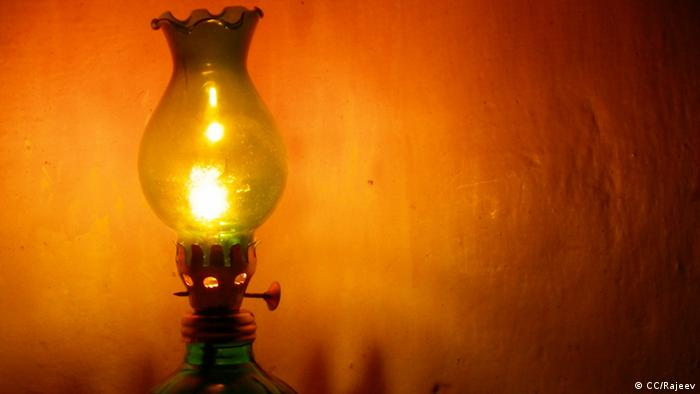 A lit kerosene lamp stands by the wall