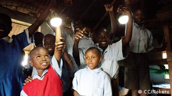 Children hold LED lamps in the air (Foto: CC/Nokero http://www.flickr.com/photos/nokero/8030478918/sizes/h/in/photostream/ Lizens: http://creativecommons.org/licenses/by/2.0/)