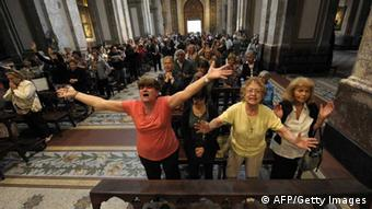 Faithful in pews raise their arms and celebrate at Metropolitan Cathedral in Buenos Aires. (Photo: JUAN MABROMATA/ AFP/Getty Images)