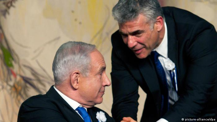 Israeli Prime Minister Benjamin Netanyahu (L) turns around as new Knesset member Yair Lapid shakes hands with the Israeli leader during a swearing-in ceremony in the Knesset (Photo: EPA/JIM HOLLANDER)
