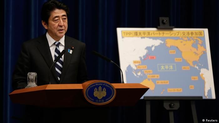 Japan's Prime Minister Shinzo Abe speaks next to a map showing participating countries in rule-making negotiations for the Trans-Pacific Partnership (TPP) during a news conference at his official residence in Tokyo March 15, 2013. Abe announced on Friday that Tokyo will seek to join talks on a U.S.-led Pacific free trade pact which proponents say will tap vibrant regional growth, open Japan to tough competition and boost momentum for reforms needed to revive the long-stagnant economy. REUTERS/Toru Hanai (JAPAN - Tags: BUSINESS POLITICS)