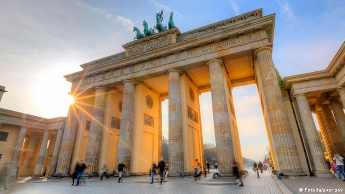 Berlin's Brandenburg Gate, with the sun shining in the background and pedestrians/tourists walking through. (Fotolia/sborisov)