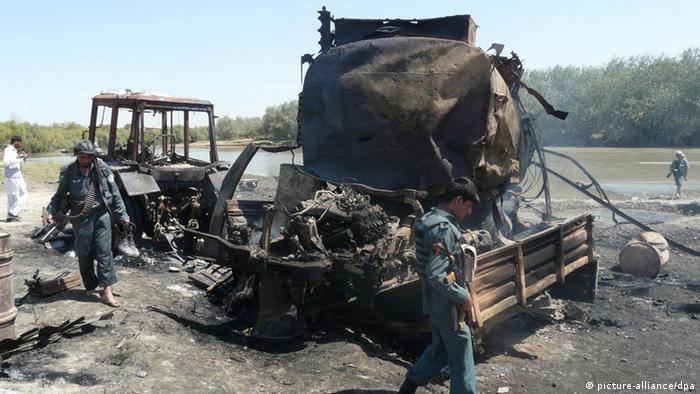 Security forces inspect the burned-out fuel tankers in Kunduz following the 2009 bombing Photo: EPA/JAWED KARGAR dpa +++(c) dpa - Bildfunk+++