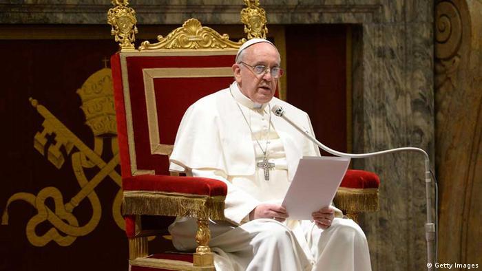 Papst Franziskus auf einem rot-goldenen Stuhl spricht in ein Mikrofon.
