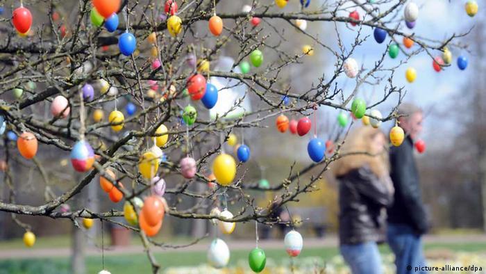 Ein Baum mit farbigen Ostereiern und Spaziergänger Foto: Maurizio Gambarini dpa/lbn