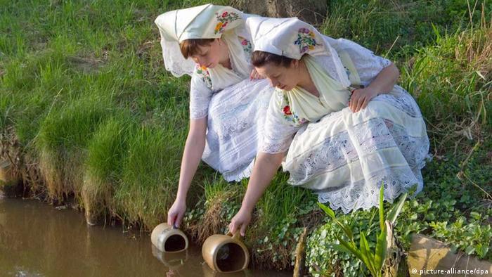 Zwei junge Sorben-Mädchen in Tracht beim Osterwasser schöpfen Foto: Peter Becker/lbn