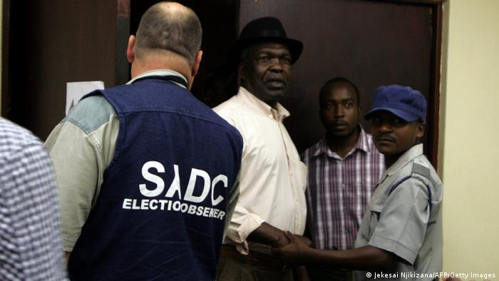 An election observer from the Southern African Development Community talks to three men