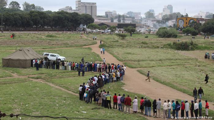 Zimbabweans wait in a queue to cast their votes