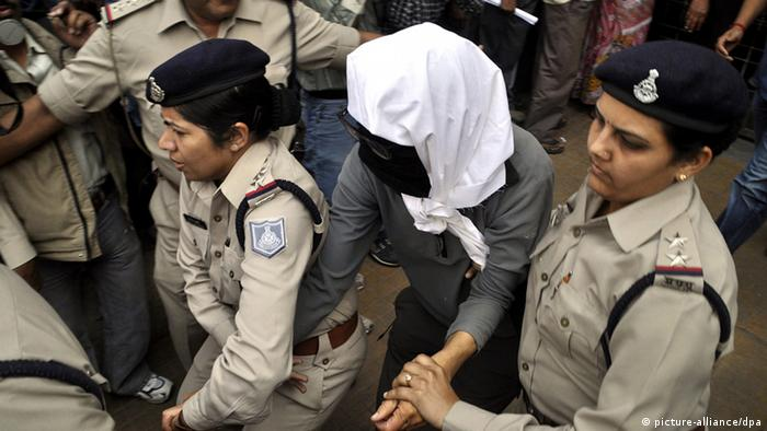 epa03627047 A Swiss woman (C), who was allegedly gang raped, is escorted by police women as she is being taken for a medical examination at a hospital in Gwalior, Madhya Pradesh, India, 16 March 2013. A group of eight men allegedly raped a 39-year-old Swiss tourist and assaulted her husband in the central Indian state of Madhya Pradesh, police said 16 March. The crime took place at a village near Datia town late 15 March, said district superintendent of police CS Solanki. EPA/SANJEEV GUPTA +++(c) dpa - Bildfunk+++