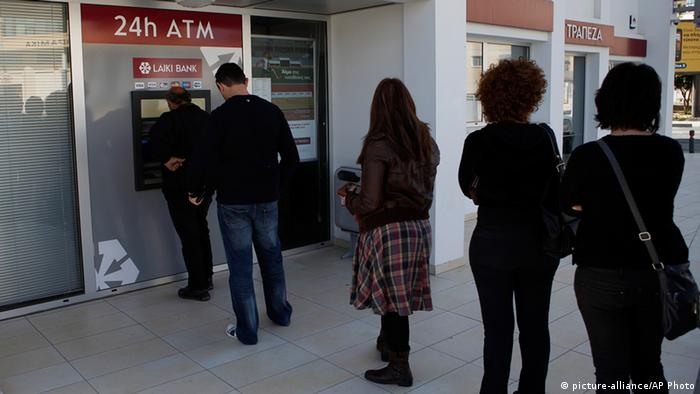 People queue to use an ATM machine outside of a Laiki Bank branch in Larnaca, Cyprus (AP Photo/Petros Karadjias)