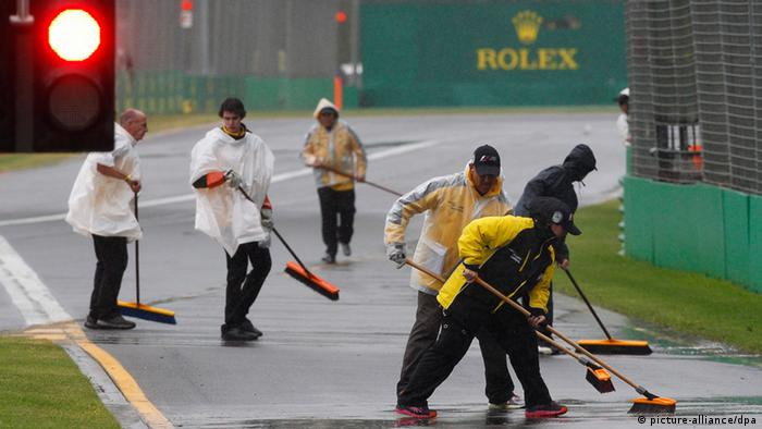 Marshals try to clear water from the pit lane exit before the qualifying session of the Australian Formula One Grand Prix at the Albert Park circuit in Melbourne, Australia, (Photo: EPA/BRANDON MALONE/DW)