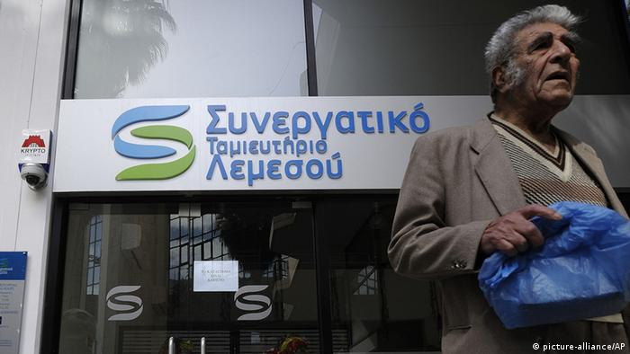 An elderly man passes by a cooperative bank in Limassol, Cyprus (Photo: AP Photo/Pavlos Vrionides)
