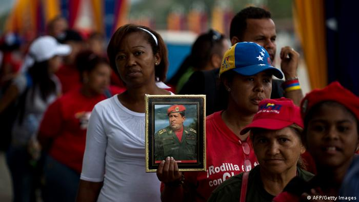GettyImages 163699225 Supporters of late Venezuela's President Hugo Chavez wait for their turn to pay their last homage to their leader, in Caracas, on March 14, 2013. The process of embalming Chavez's remains specially so that he could be viewed like Lenin started too late, acting President Nicolas Maduro said earlier this week. The government had said it wanted Chavez's supporters to be able to visit the late standard-bearer of the Latin American left forever in the wake of his March 5 death from cancer after 14 years in power. AFP PHOTO/RONALDO SCHEMIDT (Photo credit should read Ronaldo Schemidt/AFP/Getty Images)