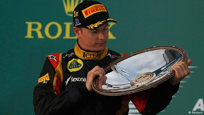 Lotus Formula One driver Kimi Raikkonen of Finland looks at his trophy after winning the Australian F1 Grand Prix at the Albert Park circuit in Melbourne March 17, 2013. REUTERS/Daniel Munoz (AUSTRALIA - Tags: SPORT MOTORSPORT F1)