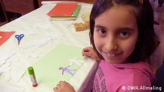 A little girl smiles as she looks up from a drawing (c) Anne Allmeling, Deutsche Welle
