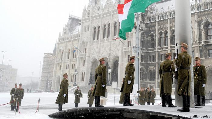 The Hungarian national flag is hoisted during heavy snowing to mark the national holiday, the 165th anniversary of the outbreak of the 1848 revolution and war of independence against the Habsburg rule in front of the Parliament building in Budapest, Hungary, 15 March 2013. EPA/IMRE FOLDI