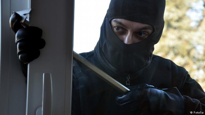 A burglar with a mask over his face breaks into an appartment (symbol). (Photo: Dan Race - Fotolia)