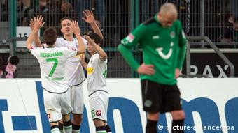 Gladbach players celebrate Luuk de Jong's goal, with a despondent Hannover player in the foreground. (Photo: Bernd Thissen/dpa)