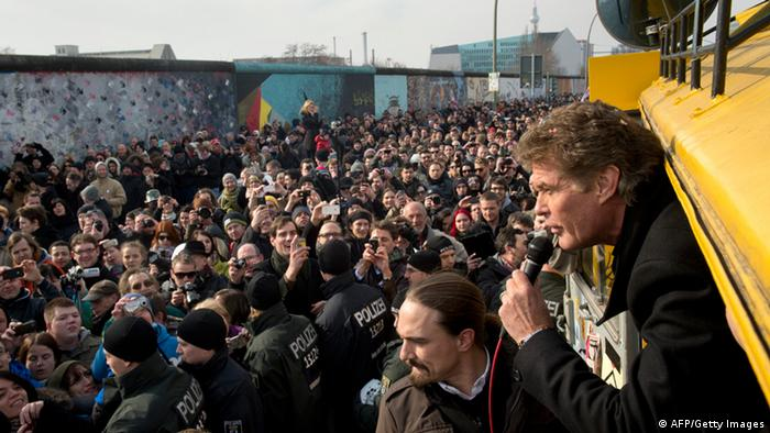GettyImages 163880303 People take pictures of US actor and singer David Hasselhoff as he talks from a van at the East Side Gallery on March 17, 2013 in Berlin, Germany to protest the planned demolition of a part of these remains of the former Berlin Wall. Thousands of people gathered as the former Bay watch star came to the German capital to lend his support to the movement that wants to preserve the 1,3km long stretch of the cold war symbol and keep the land along river Spree as public land. AFP PHOTO / ODD ANDERSEN (Photo credit should read ODD ANDERSEN/AFP/Getty Images)