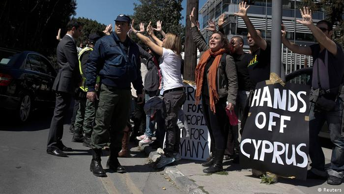 Demonstrators raise their arms in protest as Cypriot President Nicos Anastasiades's convoy drives to the parliament in Nicosia March 18, 2013. Cypriot ministers rushed on Monday to revise a plan to seize money from bank deposits as part of an EU bailout, in an effort to ensure lawmakers supported it in a vote later in the day. The weekend announcement that Cyprus would impose a tax on bank accounts as part of a 10 billion euro ($13 billion) bailout broke with previous practice that depositors' savings were sacrosanct and sent a shiver across the bloc, causing the euro to tumble and stock markets to dive. REUTERS/Yorgos Karahalis (GREECE)