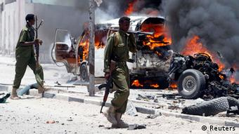 Policemen walk past the scene of an explosion near the presidential palace in Somalia's capital Mogadishu, March 18, 2013. A car bomb exploded near the presidential palace in the Somali capital Mogadishu on Monday, killing at least 10 people in a blast that appeared to target senior government officials, police said. REUTERS/Feisal Omar (SOMALIA - Tags: CIVIL UNREST CRIME LAW POLITICS)