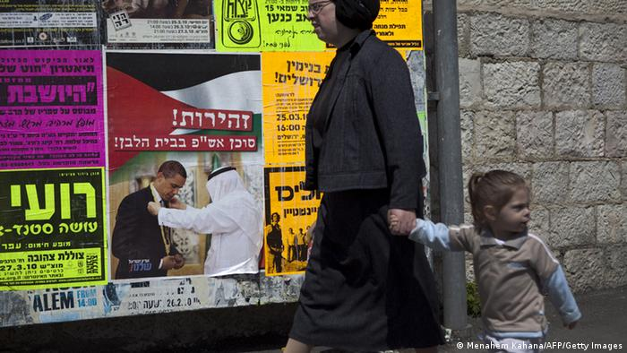An Israeli woman and a child walk past a poster in Jerusalem on March 22, 2010 bearing a picture of Saudi King Abdullah bin Abdul Aziz presenting US President Barack Obama (L) with the King Abdul Aziz Order of Merit and Hebrew writing that reads Caution, a PLO agent in the White House.? 