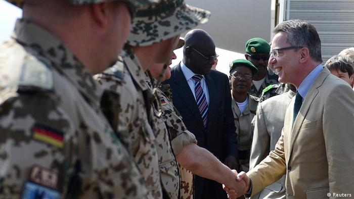 German Defence Minister Thomas de Maiziere (R) meets with members of a German Bundeswehr soldier advisory group, on arrival at the airport in Bamako March 18, 2013. REUTERS/Oliver Lang/Pool (MALI)