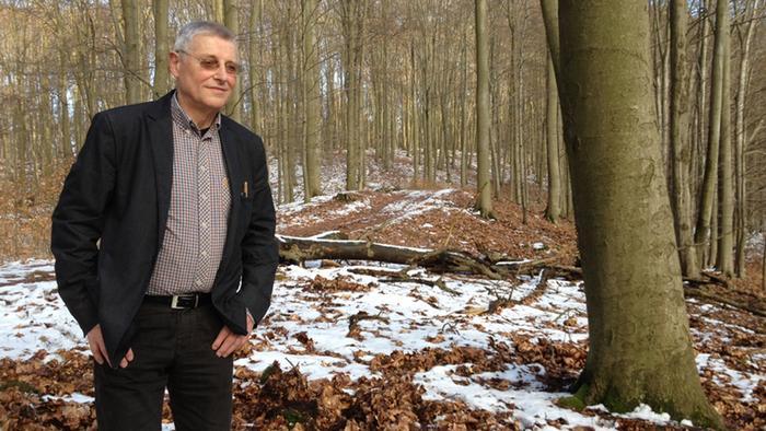 Hans-Jürgen Bewer steht im Wald. Überall liegen Schneereste.