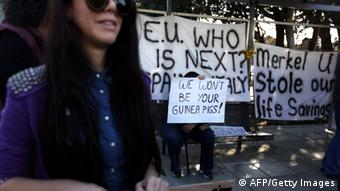 Cypriots hold placards during a protest against an EU bailout deal outside the parliament in Nicosia on March 18, 2013. Photo: PATRICK BAZ/AFP/Getty Images