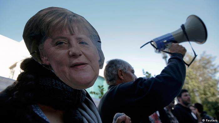 A protester wearing a mask of German Chancellor Angela Merkel takes part in an anti-bailout rally outside the parliament in Nicosia March 18, 2013. Cypriot ministers were trying to revise a plan to seize money from bank deposits before a parliamentary vote on Tuesday that will secure the island's financial rescue or could lead to its default, with reverberations across the euro zone. REUTERS/Yorgos Karahalis (CYPRUS - Tags: POLITICS CIVIL UNREST BUSINESS)