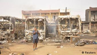 A man stands in front of some burnt buses at a motor park in Sabon Gari, after Monday's explosions in Kano March 19, 2013. Five explosions at a bus park in northern Nigeria's main city of Kano killed at least 25 people on Monday, a Reuters witness said, in an area where Islamist sect Boko Haram is waging an insurgency against the government. The coordinated bombing came as an audio tape emerged of a man saying he was the father of a family of seven French tourists kidnapped by Boko Haram militants. REUTERS/Stringer (NIGERIA - Tags: CIVIL UNREST POLITICS)