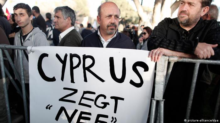 Protester stand in front of a banner which reads Cyprus Says No during a crucial parliamentary vote on a plan to seize a part of depositors' bank savings, in central Nicosia, Tuesday, March 19, 2013. The Cypriot government sought Tuesday to shield small savers from a plan that is intended to raise euro 5.8 billion ($7.5 billion) toward a financial bailout by seizing money from bank accounts. The plan, which is part of a larger bailout package being negotiated with other European countries, has been met with fury in Cyprus and has sent jitters across financial markets. (AP Photo/Petros Giannakouris)