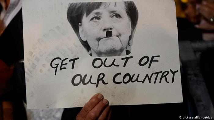 A protestor in front of the parliament building holds a poster showing German Chancellor Angela Merkel after the Cyprus Parliament rejected the bailout deal, Copyright: EPA/FILIP SINGER